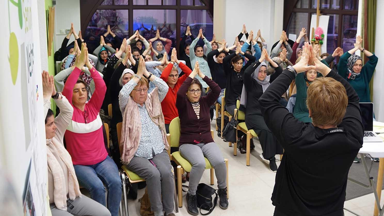 Etwa 20 Frauen und Mütter sind zu sehen. Sie sitzen im Publikum und halten die Arme in Yoga-Grußhaltung nach oben.