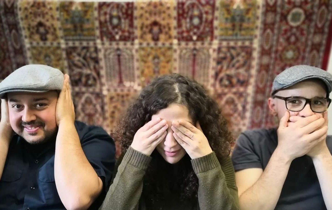 Drei Mitarbeitende von Coach e.V.. Rechts ein Mann, der sich den Mund zuhält. In der Mitte eine Frau, die sich die Augen zuhält und links ein Mann, der sich die Ohren zuhält und dabei lächelt.