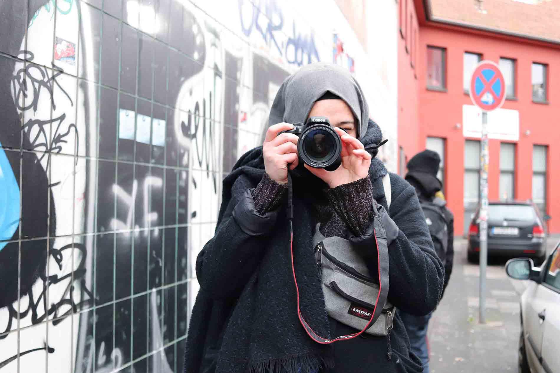 Mädchen mit Kopftuch beim Fotografieren