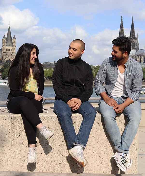 Jugendforum Köln-Team sitzt auf einer Mauer im Hintergrund ist der Kölner Dom zu sehen.