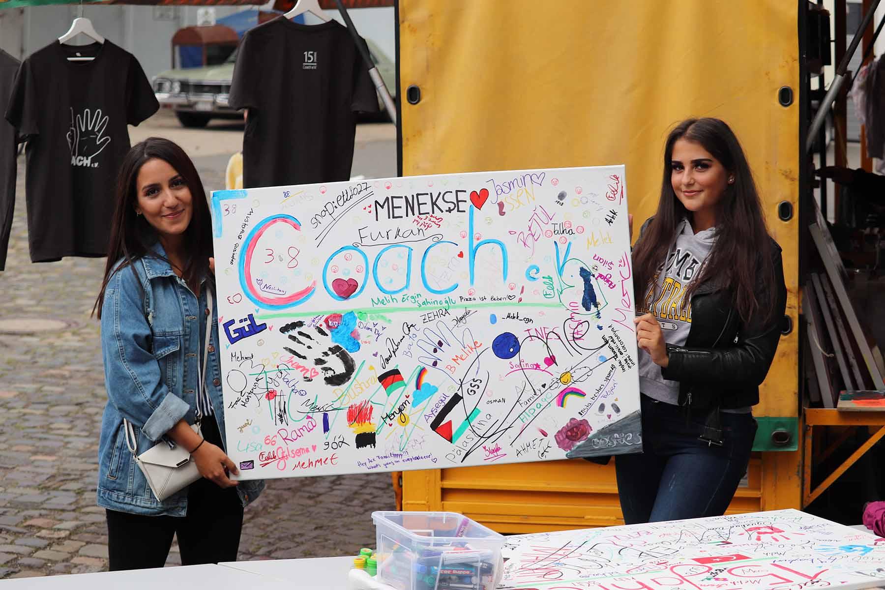 """Zwei Mädchen halten ein Schild hoch """"15 Jahre Coach e.V."""""""