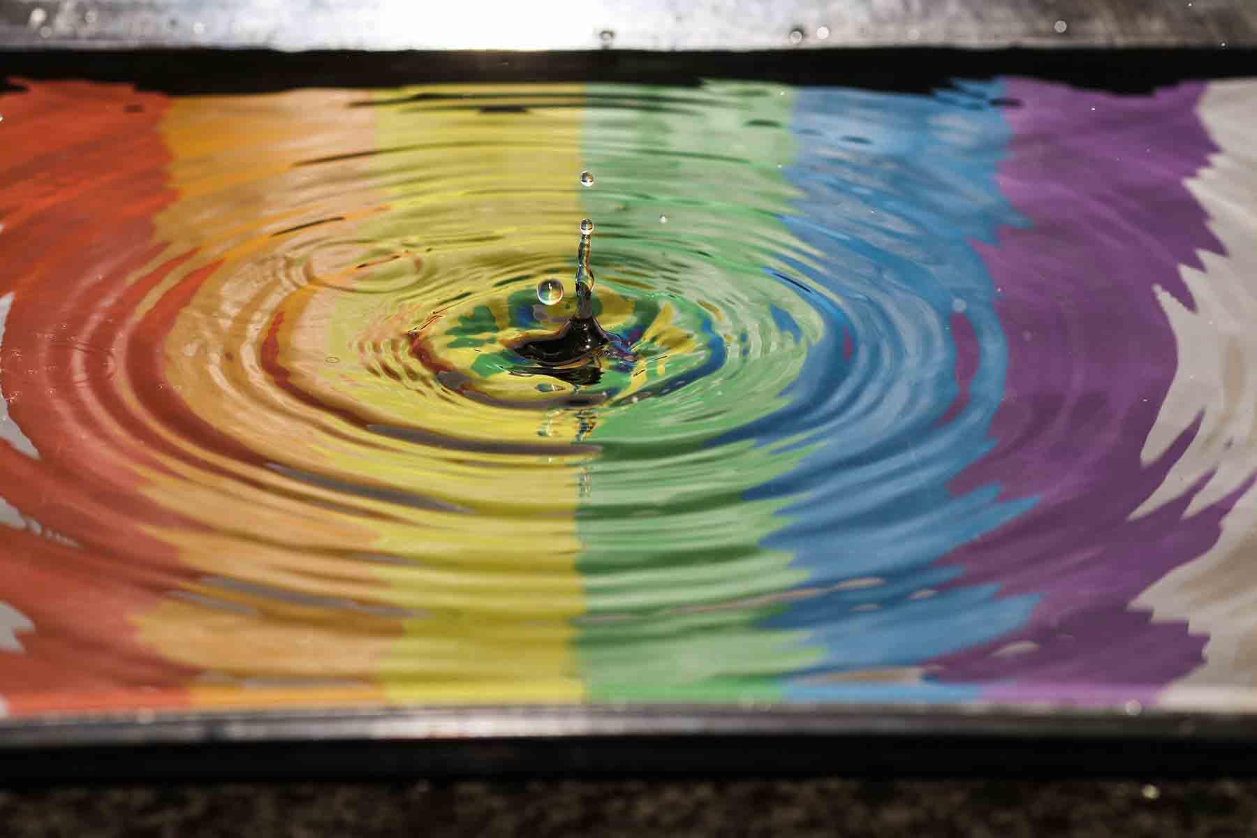 Regenbogenfarben reflektiert auf einer Wasserpfütze